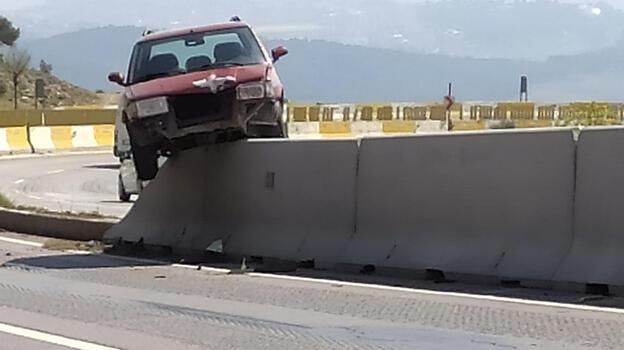 Refüjdeki beton bariyere çıkan otomobil, asılı kaldı
