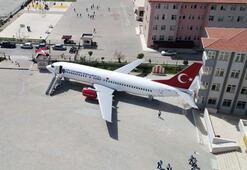 Okulun bahçesinde dev uçağı görenler şaşkına dönüyor